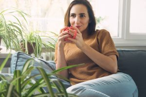 Content woman drinks coffee on her couch after finding relief from PTDS symptoms with EMDR therapy in Burke, VA at Nova Terra Therapy 22015