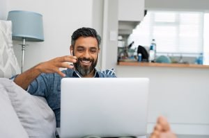 latino man sitting at the computer looking happy during online therapy in Virginia with an online therapist from Nova Terra Therapy