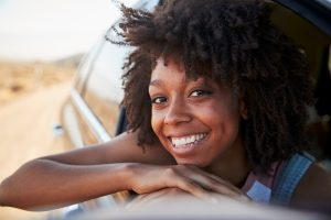 happy black woman leans out of a car window smiling after Cognitive behavioral therapy CBT in burke VA from a therapist at Nova Terra Therapy 22015
